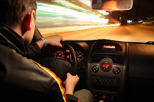 A man driving a sports car fast at night