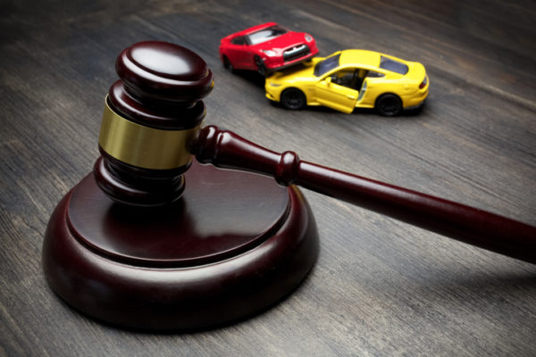a gavel and two crashed cars