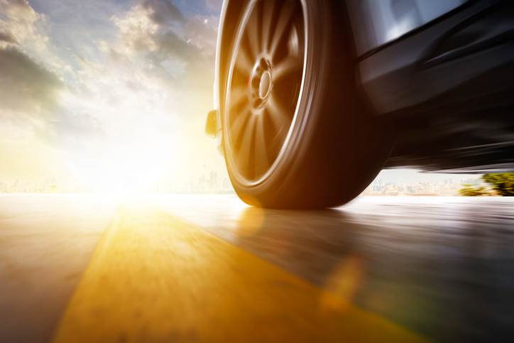 ground level view of the tire of a speeding car at sunset
